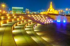 Amphitheater in Doha night. Stairs of amphitheater at Souq Waqif Garden near Doha Corniche with Doha mosque illuminated at night. Doha city center in Qatar royalty free stock image