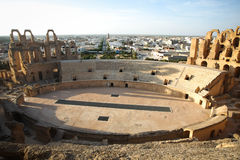 Amphitheatre with El Djem city skyline. Central podium of roman biggest amphitheater in africa with city skyline of El Djam in the background, Tunisia royalty free stock photo