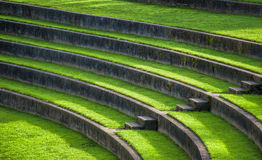 Amphitheatre Outdoor Seating. Sunlight leads they eye down the steps of the outdoor grass seating in a park Amphitheatre royalty free stock photo