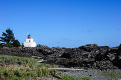 Amphitrite lighthouse at low tide. Uclulet lighthouse at low tide with the Rocky shore royalty free stock photo