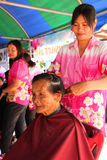 Amphoe Yim Mobile Project. BORABUE, MAHASARAKHAM - NOVEMBER 16 : The unidentified barber is cutting an old woman hair in Amphoe Yim Mobile Project on November 16 royalty free stock image