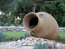 Amphora. Large old amphorae placed in the garden with flowers Stock Image