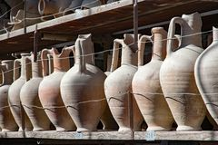 Amphora in a row on a shelf Stock Image