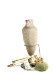 Amphora with shells. Two-handled jar used in ancient Greece and Rome with some sea shells on white background stock photo
