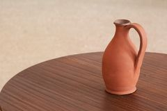 Amphora on table. Reduced picture of amphora on brown table Stock Photo