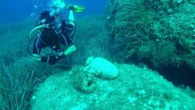 Amphorae su una roccia e subacqueo li indaga stock footage