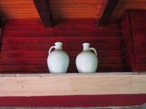 Amphoras sur l'étagère avec le fond en bois d'acajou Images stock