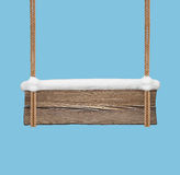 Ampia insegna di legno con neve che appende sulle doppie corde Fotografie Stock Libere da Diritti