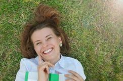 Ampia ragazza sorridente felice con il libro che si trova sull'erba nel parco Fotografia Stock