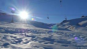 Ampia vista di muovere l'ascensore di sci vuoto e uno snowboard dell'uomo dalla montagna nevosa su fondo stock footage