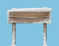 Ampio cartello di legno con neve isolata sul blu Immagini Stock