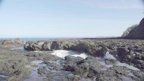 Ampio colpo di slomo delle onde di oceano turbolente che si schiantano su una riva di mare rocciosa stock footage