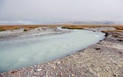 Ampio fiume rapido bianco in mezzo della valle su un fondo della collina rocciosa Fotografie Stock