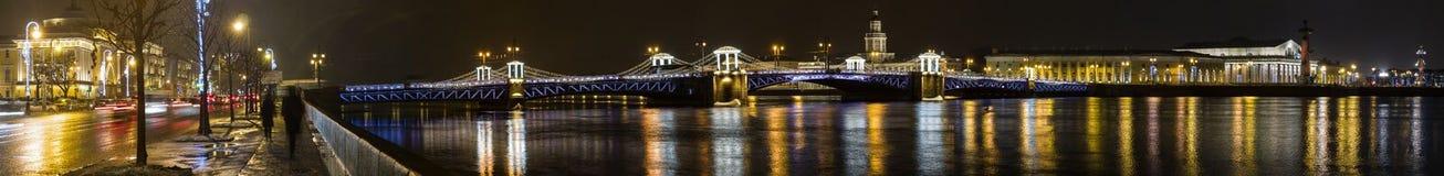 Ampio panorama di notte sul ponte, su Neva River e sulle costruzioni aperti illumunated del palazzo sull'argine fotografie stock
