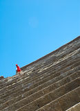 Ampitheatre at Ostia Antica. Blue sky & gray stone, with red dressed girl at Ostia Antica, Italy Royalty Free Stock Image