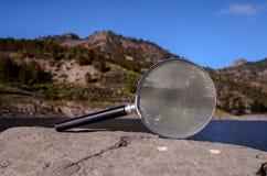 Amplie a lupa de vidro na rocha vulcânica imagens de stock