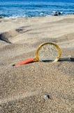 Amplie o vidro na praia da areia foto de stock