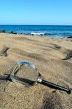 Amplie o vidro na praia da areia fotografia de stock royalty free