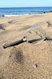 Amplie o vidro na praia da areia imagem de stock