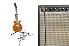Amplificador y guitarra eléctrica en fondo Fotografía de archivo