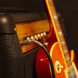 Amplifier for electric guitar with guitar on the black background. Shallow depth of field, low key, close up Royalty Free Stock Photos