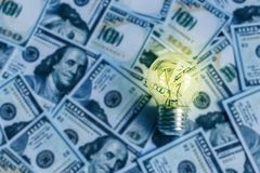 Ampola ardente no fundo dos dólares, eletricidade cara Fotografia de Stock