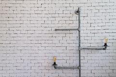 Ampola com a tubulação do metal sobre o fundo do tijolo Fotos de Stock