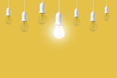 Ampola da diferença no fundo amarelo Conceito de ideias novas foto de stock royalty free