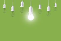 Ampola da diferença no fundo verde Conceito de ideias novas imagem de stock