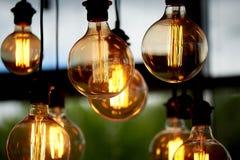 Ampola de Edison que pendura em um fio longo Luz amarela morna acolhedor retro Imagem de Stock Royalty Free
