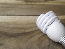 Ampola de poupança de energia no fundo de madeira Imagens de Stock Royalty Free