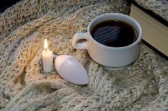 Ampola de poupança de energia, vela, copo de café e livro no fundo de uma cobertura morna imagem de stock