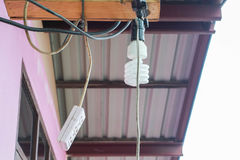A ampola e a tomada espirais penduram no telhado da casa Fotografia de Stock