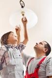 Ampola em mudança do pai e do filho em uma lâmpada do teto Foto de Stock Royalty Free