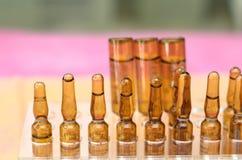 Ampola médicas amarelas no fundo cor-de-rosa Imagens de Stock