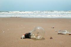Ampola velha em um Sandy Beach próximo ao mar Poluição de um litoral foto de stock