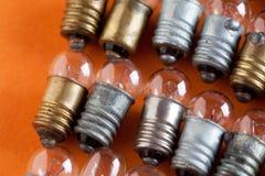 Ampolas ajustadas no fundo de papel alaranjado Lâmpadas coloridas do vintage do bronze e da prata do ouro Profundidade rasa da vi Imagem de Stock