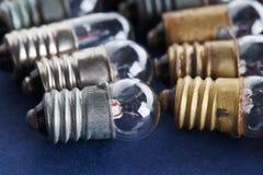 Ampolas ajustadas no fundo do papel azul Lâmpadas coloridas do vintage do bronze e da prata do ouro campo macro da profundidade r Imagem de Stock