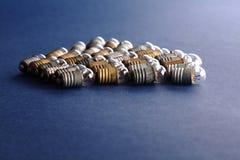 Ampolas ajustadas no fundo do papel azul Lâmpadas coloridas do vintage do bronze e da prata do ouro campo macro da profundidade r Foto de Stock