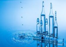 Ampolas e seringa médicas no fundo da água azul com respingo e gotas Fotografia de Stock Royalty Free
