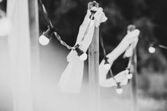 Ampolas em um fio com ornamento brancos e tochas em um beac Imagem de Stock