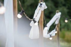 Ampolas em um fio com ornamento brancos e tochas em um beac Fotografia de Stock