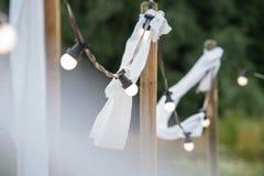 Ampolas em um fio com ornamento brancos e tochas em um beac Fotos de Stock Royalty Free