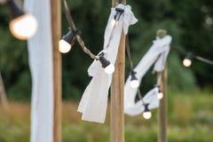 Ampolas em um fio com ornamento brancos e tochas em um beac Foto de Stock
