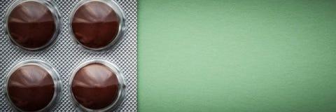 Ampolla con las tabletas marrones en un fondo verde fotografía de archivo