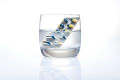 Ampolla de píldoras azules y amarillas en un vidrio de agua fotos de archivo