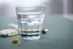 Ampolla dos de la medicina amarilla de las tabletas de las píldoras con el vaso de agua fotos de archivo libres de regalías