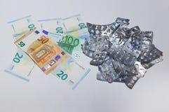 Ampollas vacías de píldoras y dinero del euro en un fondo blanco El concepto de alto coste de drogas imagen de archivo