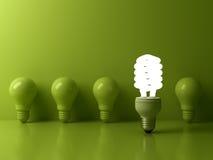 Ampoule économiseuse d'énergie d'Eco, une ampoule fluorescente compacte rougeoyante se tenant des ampoules incandescentes non all Photographie stock