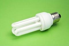 Ampoule économiseuse d'énergie sur la surface verte Photographie stock